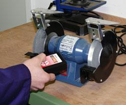 Hier sehen Sie das LED Handstroboskop PCE-LES 100 bei der Überprüfung einer Schleifmaschine