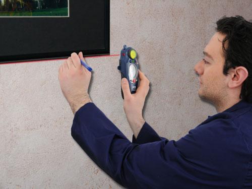 Der Wandscanner im Einsatz bei der Ausrichtung eines Bildes mit   Hilfe des Linienlasers.