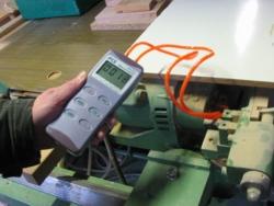 Das Druckmessgerät PCE-P beim messen des Drucks an einer Maschine