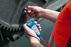 Das Farbschichtdicke-Messgerät bei einer Farbschichtmessung an einem Zahnrad.