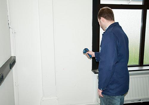 Der Energiespar-Detektor bei der Überprüfung von Wänden in einem Altbau.