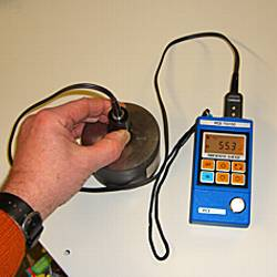 the PCE-TG100 material thickness meter measuring a steel plate
