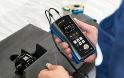 Dickenmessgerät bei der Qualitätskontrolle in der Kunststoffindustrie.